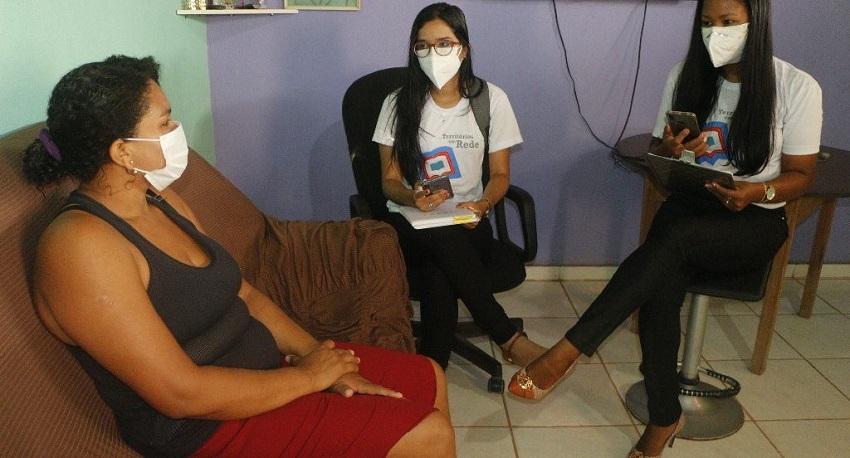 """Em sala de estar, duas integrantes do projeto """"Territórios em rede"""" conversam com a responsável por estudante. Fim da descrição."""