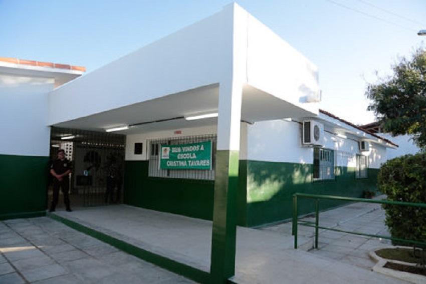 """Parte externa da escola Cristina Tavares com pintura em verde e branco e uma faixa escrito """"Bem-vindos à escola Cristina Tavares"""". Fim da descrição."""