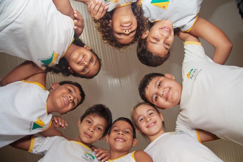 Oito crianças uniformizadas estão abraçadas em formato de roda, sorrindo para foto tirada em ângulo de baixo para cima. Fim da descrição.